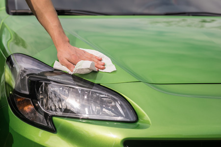 Spring cleaning. Young boys hand  is polishing the green car. Banco de Imagens