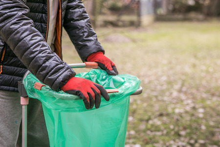 The hands of a mature man in working gloves fasten a green sack on the rack during the springtime gardening