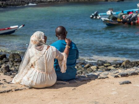 A view of a Senegalese couple in wedding dress sitting by the ocean on the island of Goree.