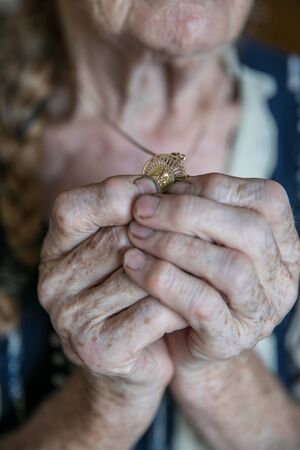 Hands of an old woman praying and holding a gold medal with Our Lady Zdjęcie Seryjne