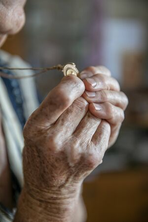 Hands of an old woman praying and holding a gold medal with Our Lady