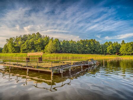Wooden jetty on a beautiful lake in Warmia. Rumian Lake. Warmia and Masuria. Poland.