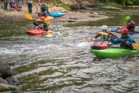 Jozefow, Poland - May  12: Water canoeing, extreme kayaking. Kayakers  in a small sport kayaks are practicing  an approach to a cascade on the Swider River in Poland