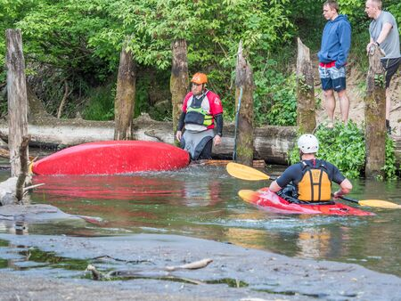 Józefów, Poland - May 12: canoeing, extreme kayaking. The guy in a small sport kayak is practicing with coach how to overcome a difficult obstacle on the Swider River in Poland Editorial