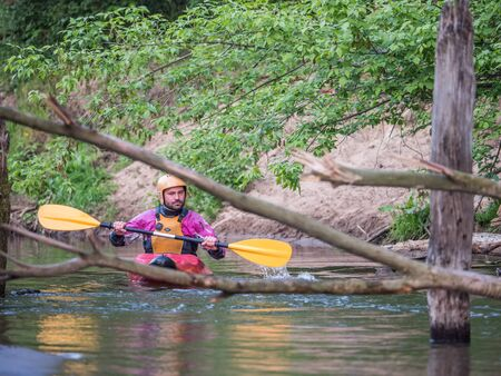 Józefów, Poland - May 12: canoeing, extreme kayaking. The guy in a small sport kayak is overcomuing  a difficult obstacle on the Swider River in Poland Editorial