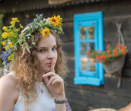 Beautiful girl in wreath of field flowers during Kupala night. Poland