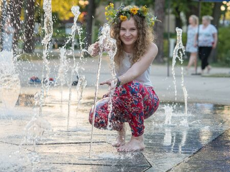 Beautiful girl in wreath of field flowers playing with water during Kupala night. Poland 写真素材