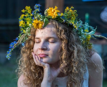 Beautiful girl in wreath of field flowers dreaming during Kupala night. Poland