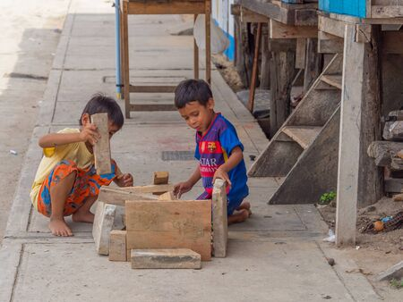 Belen, Iquitos, Peru - September 25, 2018: Two boys playing with pieces of wooden boards on the street. South America 報道画像
