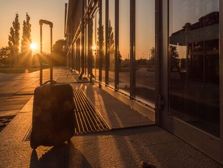 Silhouette of suitcase at sunrise next to the train station.  Warsaw. Poland 스톡 콘텐츠