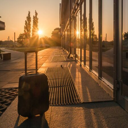 Silhouette of suitcase at sunrise next to the train station.  Warsaw. Poland Stock Photo