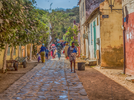 Goree, Senegal- February 2, 2019: Everyday life and street with a cobblestone road between colorful houses on the island of Goree. Gorée. Dakar, Senegal. Africa. Reklamní fotografie - 130291689
