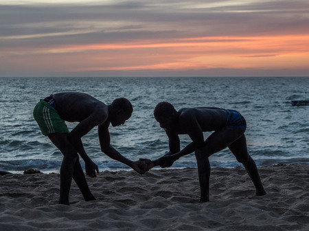 Nianing, Senegal - January 24, 2019: Unidentified silhouettes of wrestlers trained on the beach during the sunset. Senegalese wrestling is a national sport in Senegal. Africa. Standard-Bild - 130291756