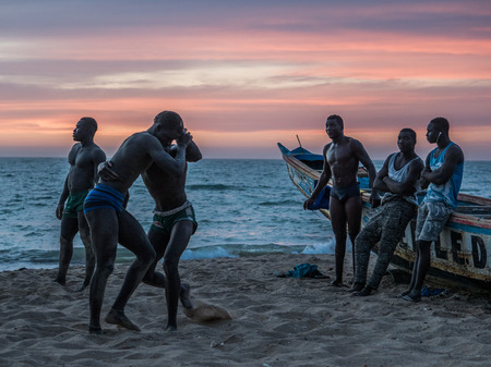 Nianing, Senegal - January 24, 2019: Unidentified silhouettes of wrestlers trained on the beach during the sunset. Senegalese wrestling is a national sport in Senegal. Africa. Standard-Bild - 130291760