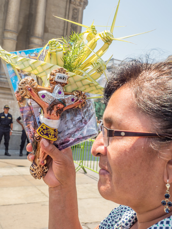 Lima, Peru - March 29, 2018: Peruvian woman showing an Easter palm on the street of Lima before Easter time. Maundy Thursday. Plaza de Armas, Peru, South America. Latin America