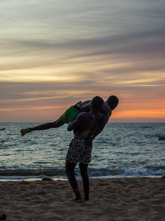 Nianing, Senegal - January 24, 2019: Unidentified silhouettes of wrestlers trained on the beach during the sunset. Senegalese wrestling is a national sport in Senegal. Africa. Standard-Bild - 130291772