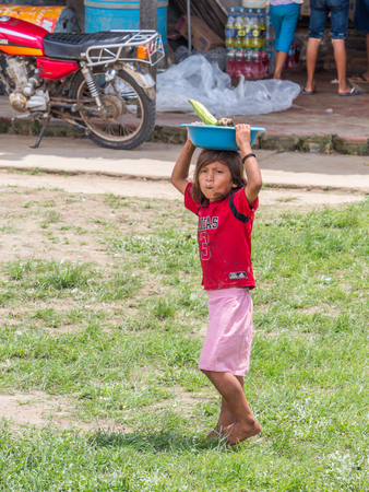 Small village by Amazon River, Peru - Dec 03, 2018: Child labor. Small girl selling the fruits on the bank of Amazon river