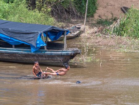 Amazon River, Peru- Dec 04, 2018:  Children swimming and jumping in the port on the Amazon river, Brazil. South America