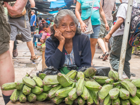 Iquitos, Peru- Mar 27, 2018: Portrait of Peruvian woman selling  bananas on the Belen market, Amazon jungle. South America. Amazonia.