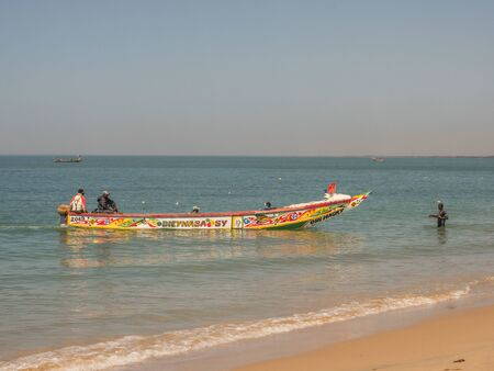 Senegal, Africa - January 2, 2019: Fishermen collecting fish from colored wooden fisher boat standing on the beach. Africa