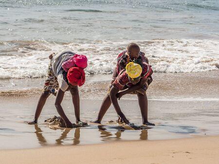 Dakar, Senegal - February 3, 2019: Senegalese women with children on their back collecting shells on a sandy beach in Dakar. Africa. 写真素材