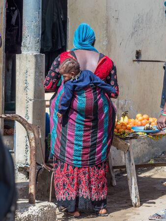 Dakar, Senegal - February 3, 2019: Senegalese woman in colorful clothes with child on her  back. Africa.