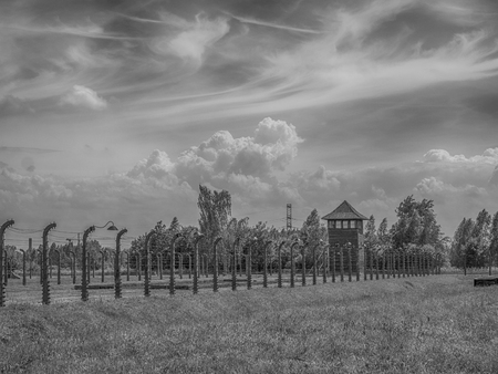 OÅ›wiÄ™cim, Poland - June 05, 2019: Electric fence with barbed wire and watchtower  at the Auschwitz-Birkenau concentration camp in OÅ›wiÄ™cim, Poland. Europe. 報道画像