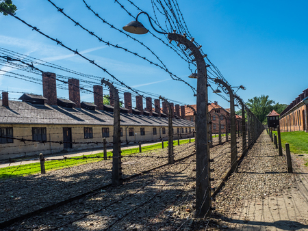 OÅ›wiÄ™cim, Poland - June 05, 2019: Electric fence with barbed wire and brick prison buildings at the Auschwitz-Birkenau concentration camp in OÅ›wiÄ™cim, Poland. Europe.