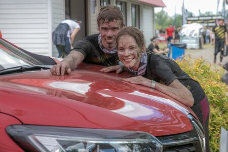 Portrait of young boy and girl  in dirty clothes with the red car after extreme running with obstacle RUNMAGEDDON
