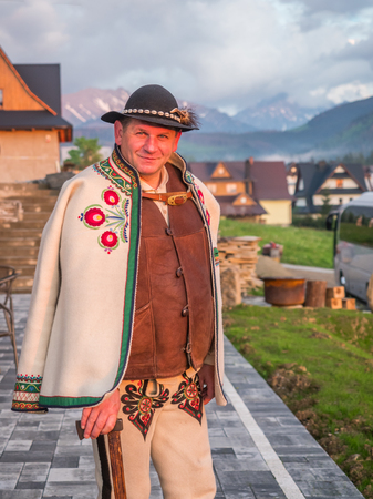 Tatry, Poland - June 03, 2019: An ethnic highlander (Góral)  in traditional goral dress with black hat and shepherd's axe in Polish Tatra mountains. Goral from Zakopane. Eastern Europe