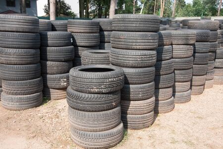 The piles of used tires lie on the square. Black rubber tire, part of the vehicle, spare part. Stok Fotoğraf - 137486455