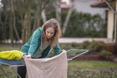 A young woman hangs the laundry in the garden