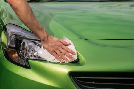 Spring cleaning. Young boys hand  is polishing the green car. Stok Fotoğraf