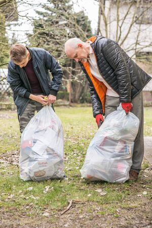 Father and son tie up plastic bags with sorted garbage. Concept of environmental protection.