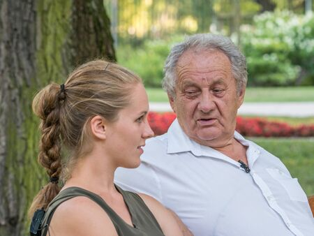 Grandpa and his granddaughter are talking and spend time together. They are sitting on the bench in the park. Intergenerational concept. Stok Fotoğraf - 137590432