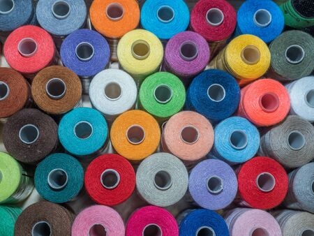 A lot of sewing colored thread. Thread reels. Colorful threads in the box. Texture of sewing accessories Stok Fotoğraf - 137486544
