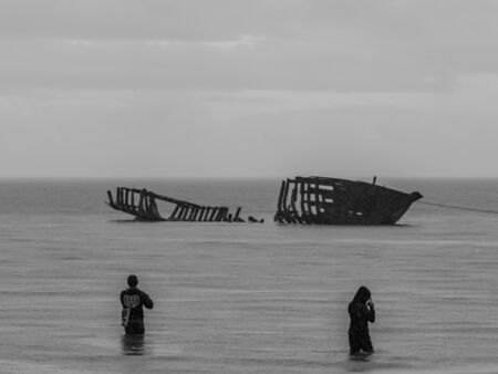 View of the silhouettes of a destroyed boat and a fishermen during high tide on the Saram Sea. Rainy weather.  Kaimana, Bird's Head Peninsula, West Papua, Indonesia, Asia. Stok Fotoğraf - 137486127