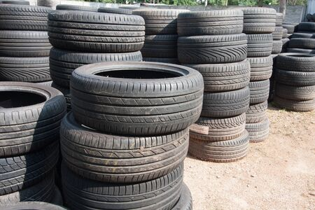 The piles of used tires lie on the square. Black rubber tire, part of the vehicle, spare part. Stok Fotoğraf