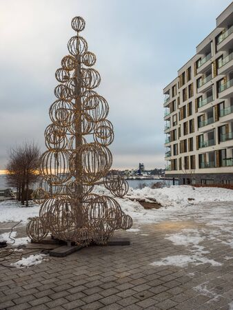Oslo, Norway - December 20, 2018: Big, white Christmas tree waiting for a Christmas time in Oslo next to the fjord. In the background modern building with view for the sea Stok Fotoğraf