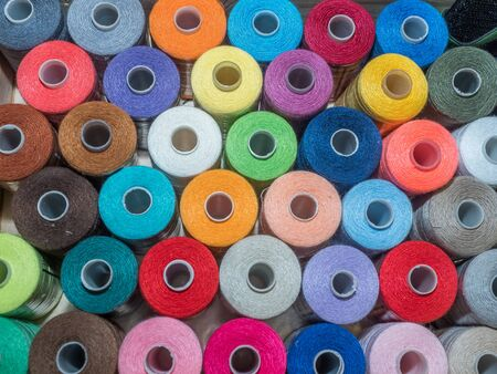 A lot of sewing colored thread. Thread reels. Colorful threads in the box. Texture of sewing accessories Stok Fotoğraf - 137486594