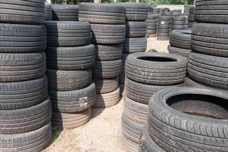 The piles of used tires lie on the square. Black rubber tire, part of the vehicle, spare part. Stok Fotoğraf - 137486715