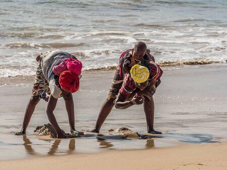 Dakar, Senegal - February 3, 2019: Senegalese women with children on their back collecting shells on a sandy beach in Dakar. Africa. Stok Fotoğraf
