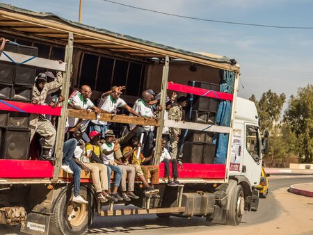 Dakar, Senegal - February 3, 2019: Africans sit on a truck, shout and show a sign of freedom during a street manifestation. Africa.