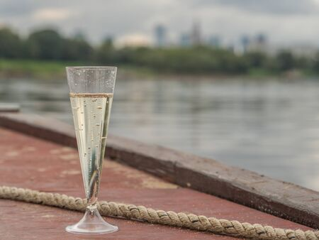 A glass of champagne in a plastic glass stands on a wooden boat. in the background a view of Warsaw, Poland,  Happy New Year. Reklamní fotografie