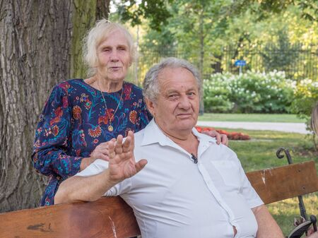 Happy elderly man and woman in the park. Seniority concept