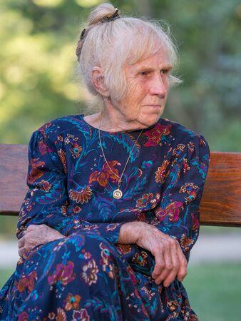 An elegantly dressed, elderly woman is sitting on a park benchis sitting on a park bench. Poland. Stok Fotoğraf - 137594059