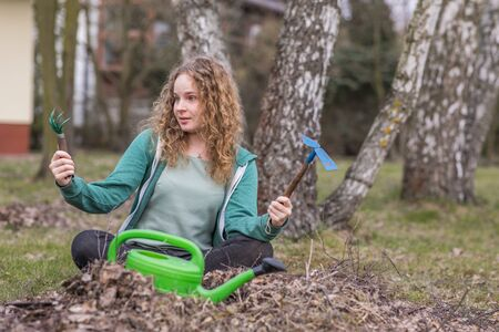 Young surprised woman during spring cleaning in the garden Stok Fotoğraf