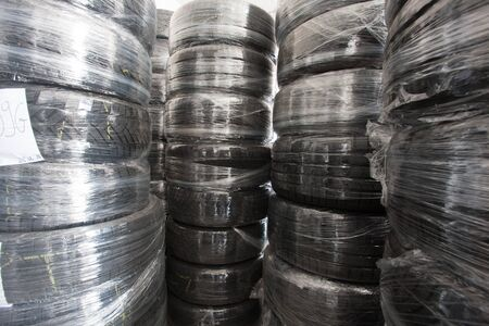 Stacks of used tires wrapped with foil are in stock. Black rubber tire, part of the vehicle, spare part.