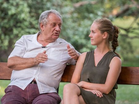 Grandpa and his granddaughter are talking and spend time together. They are sitting on the bench in the park. Intergenerational concept.