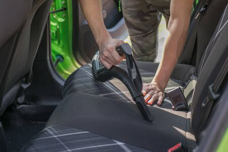 Hands of the young man cleaning Interior of car using vacuum cleaner Stok Fotoğraf